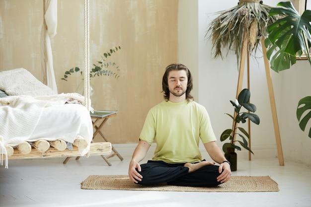 Friedlicher mann, der zu hause in der meditationshaltung sitzt, hübscher mann im lotus asna, der sich auf das konzept der atmung, der achtsamkeit konzentriert