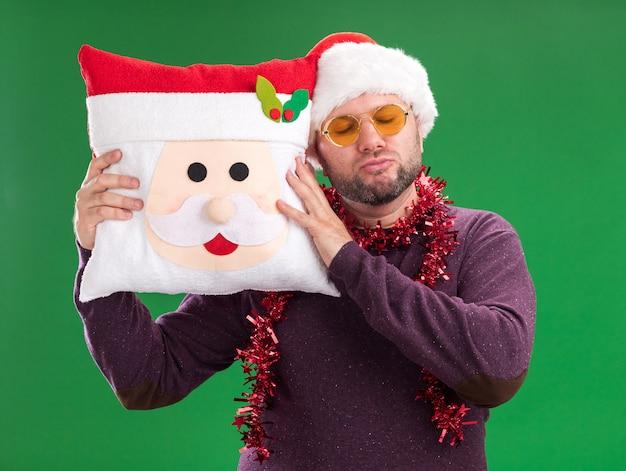Friedlicher mann mittleren alters mit weihnachtsmütze und lametta-girlande um den hals mit brille, die das weihnachtsmann-kissen hält und den kopf damit mit geschlossenen augen auf grünem hintergrund berührt
