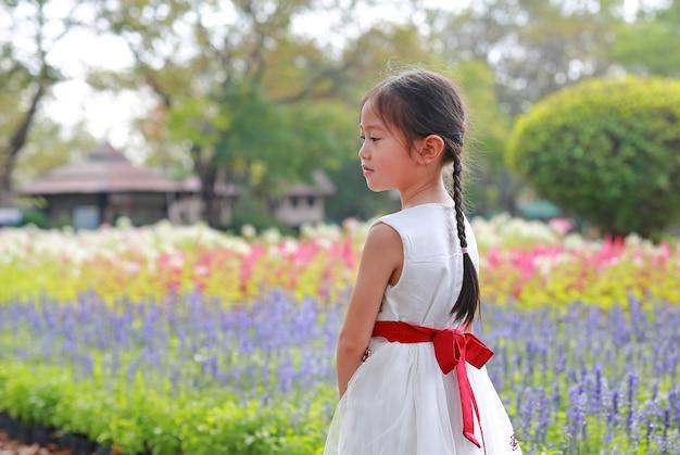 Friedliches asiatisches kleines kindermädchen, das am morgen im frischen blumengarten steht.
