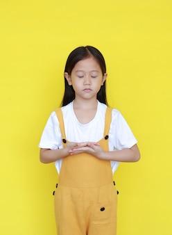 Friedliches asiatisches kleines mädchen auf gelbem hintergrund