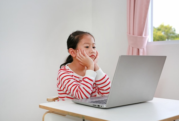 Friedliches asiatisches kleines mädchenkind, das am schreibtisch sitzt und bildschirmlaptopcomputer schaut