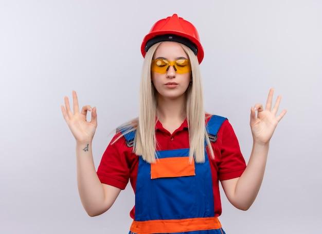 Friedliches junges blondes ingenieur-baumeistermädchen in der uniform, die schutzbrille trägt und mit geschlossenen augen über isolierten weißen raum meditiert