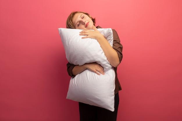 Friedliches junges blondes mädchen, das kissen umarmt, das den kopf mit geschlossenen augen darauf legt, isoliert auf rosa wand mit kopierraum