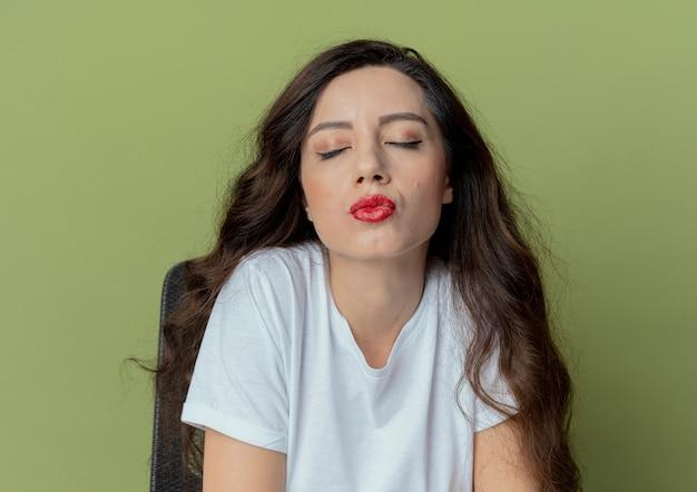 Friedliches junges hübsches mädchen, das am make-up-tisch mit make-up-werkzeugen sitzt, die kussgeste mit geschlossenen augen lokalisiert auf olivgrünem hintergrund tun