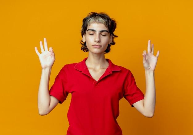 Friedliches junges kaukasisches mädchen mit pixie-haarschnitt, der mit geschlossenen augen meditiert, lokalisiert auf orange hintergrund mit kopienraum