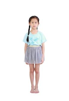 Friedliches kleines asiatisches kindermädchen, das mit zopfhaar lokalisiert über weißem hintergrund steht.