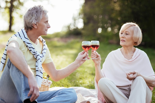 Friedliches, liebendes, älteres ehepaar, das seine liebe zum ausdruck bringt, während es ein picknick genießt und wein trinkt