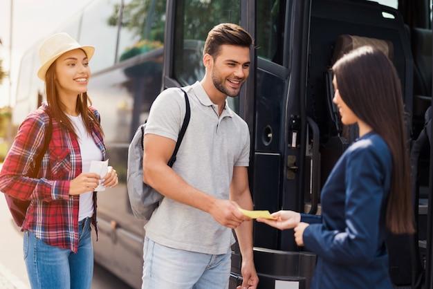 Friendly attendant schecks tickets bus service.