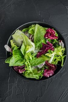Fries, römersalat und radicchiosalat, auf schwarzem hintergrund, draufsicht flach