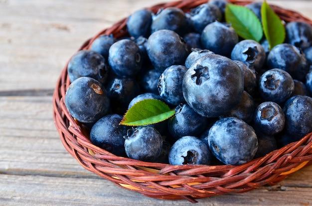 Frisch ausgewählte blaubeeren in einem korb auf altem holztisch. frische blaubeeren mit grünen blättern auf rustikaler tabelle. blaubeere. heidelbeere. konzept der gesunden ernährung, diät und ernährung.