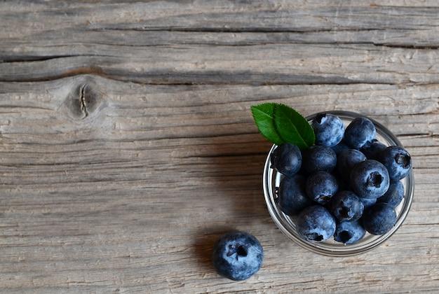 Frisch ausgewählte blaubeeren in einer glasschüssel auf altem hölzernem hintergrund. frische bio-heidelbeere. heidelbeeren.
