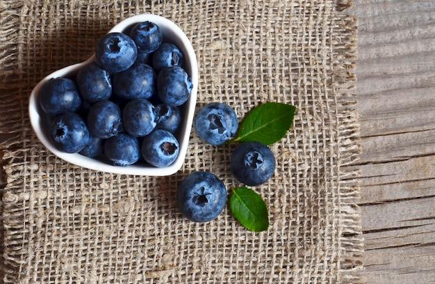 Frisch ausgewählte organische blaubeeren in einer weißen schüssel auf einem leinwandstoffhintergrund