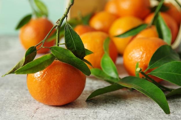 Frisch duftende mandarinen. reife saftige mandarinen mit grünen blättern auf dem tisch.