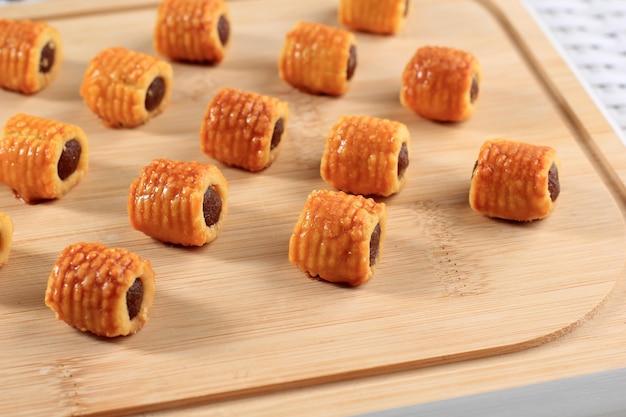Frisch gebackene ananas-tart roll cookies (tart nanas oder kuih nenas oder nastar gulung). konzept von kue lebaran auf weißem hintergrund