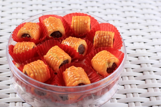 Frisch gebackene ananas-tart-roll-plätzchen (tart nanas oder kuih nenas) auf holzuntergrund. bereit zum verkauf bei eid mubarak
