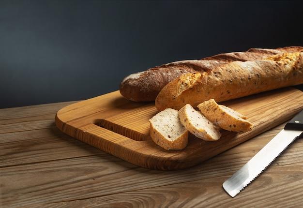 Frisch gebackene baguettes auf einem schneidebrett mit gehackten stücken auf grauem hintergrund.