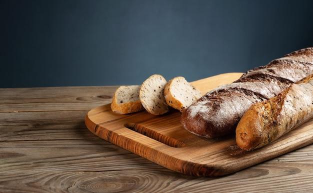 Frisch gebackene baguettes auf einem schneidebrett mit gehackten stücken