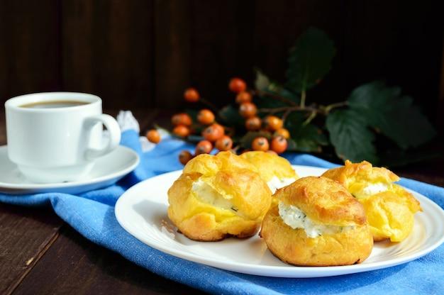 Frisch gebackene brötchen-eclairs gefüllt mit würzigem hüttenkäse und einer tasse kaffee