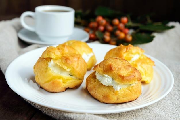 Frisch gebackene brötchen-eclairs gefüllt mit würzigem hüttenkäse und einer tasse kaffee Premium Fotos