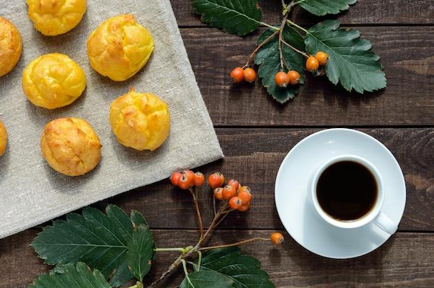 Frisch gebackene brötchen-eclairs und eine tasse kaffee auf dunklem holzhintergrund