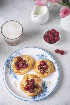 Frisch gebackene brötchen mit himbeeren und cappuccino-kaffee auf weißem tisch