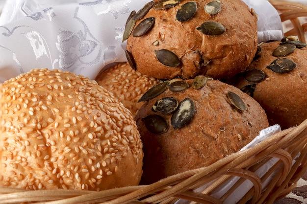 Frisch gebackene brötchen und brot in einem korb auf einer tabelle.