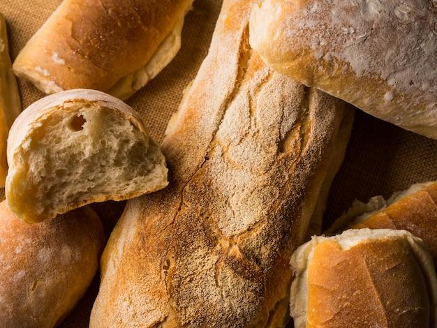 Frisch gebackene brotlaibe auf dunklem hölzernem der leinwand. italienische bäckereiprodukte der beschaffenheitsnahaufnahme
