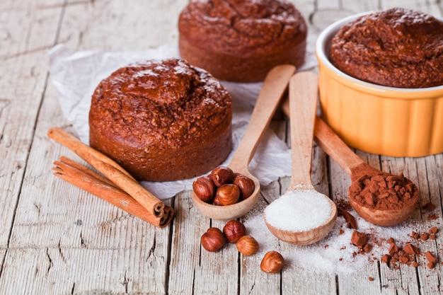 Frisch gebackene browny cakes, zucker, haselnüsse und kakaopulver