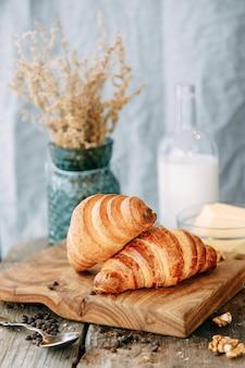 Frisch gebackene croissants auf einem holztisch. frühstück mit croissants und milch nahaufnahme.