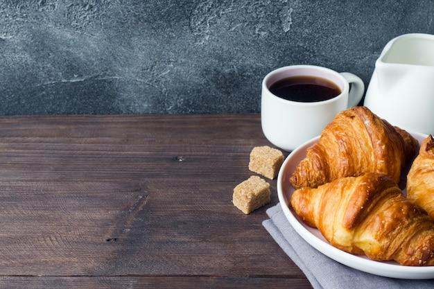 Frisch gebackene croissants auf einem teller, dunkler hintergrund,