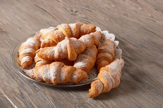 Frisch gebackene croissants auf einer runden platte. croissants auf einem holztisch