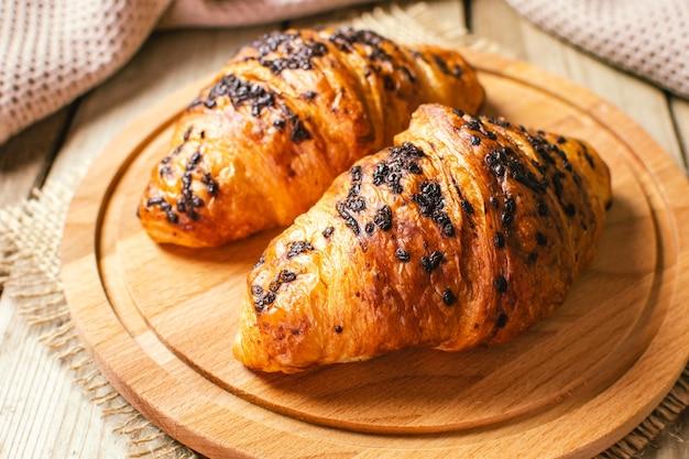 Frisch gebackene croissants auf holzschneidebrett, draufsicht. hausgemacht oder bäckerei.