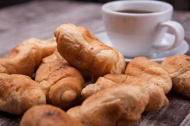 Frisch gebackene croissants auf rustikalem holztisch mit tasse kaffee. leckerer kaffee.