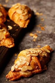 Frisch gebackene croissants, die mandeln köstlich frisch in plattenholztisch übersteigen. französisches frühstück