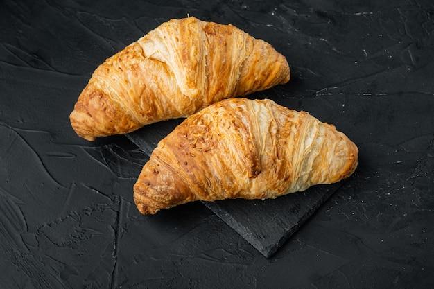 Frisch gebackene croissants eingestellt, auf schwarzem steinhintergrund
