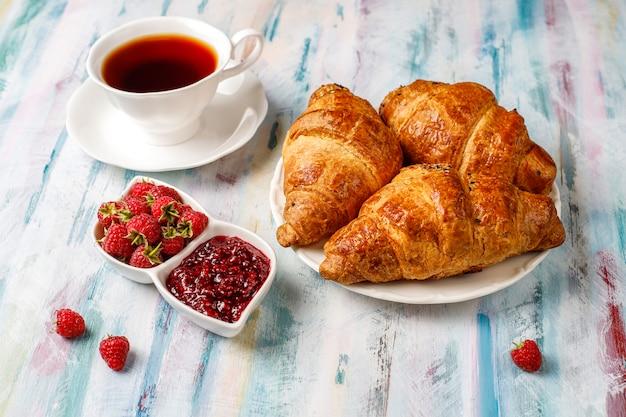 Frisch gebackene croissants mit himbeermarmelade und himbeerfrüchten.