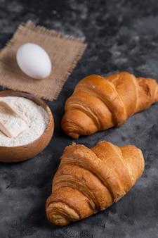 Frisch gebackene croissants mit hühnereiern und holzschale mehl.