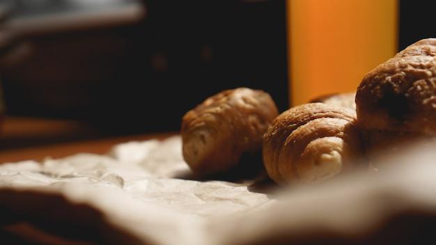 Frisch gebackene croissants mit orangensaft auf kraftpapier. nahaufnahmephotographie des frischen köstlichen nachtischs zum frühstück.