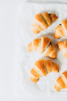 Frisch gebackene croissants mit schokoladenfüllung auf weißem hintergrund.