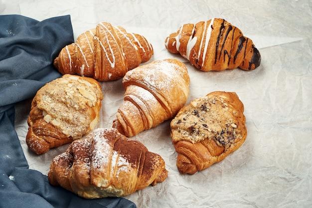 Frisch gebackene croissants mit verschiedenen füllungen auf pergament. appetitliches französisches gebäck zum frühstück. unterschiedliches sortiment, viele croissants