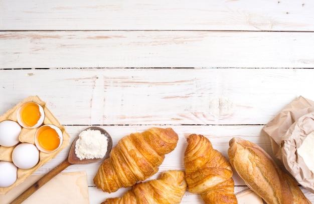 Frisch gebackene croissants und baguette mit mehl, holzlöffel, stück papier, eiern und eigelb