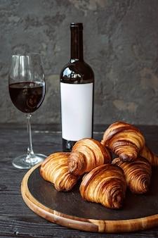 Frisch gebackene duftende croissants auf einem dunklen steinbrett, ein glas rotwein und eine flasche. romantisches abendessen.