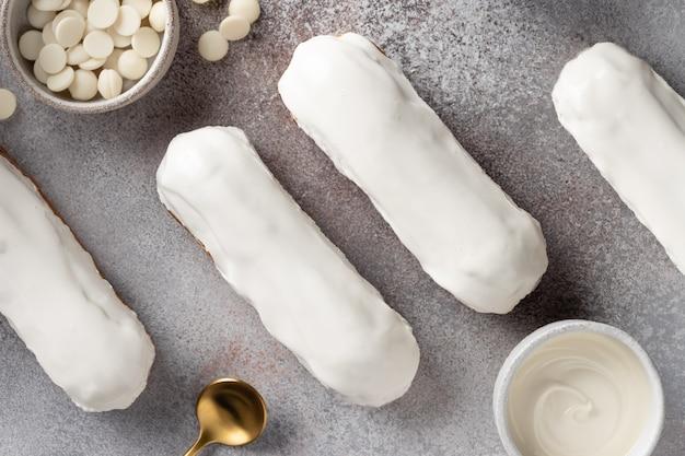 Frisch gebackene eclairs mit weißer schokolade überzogen