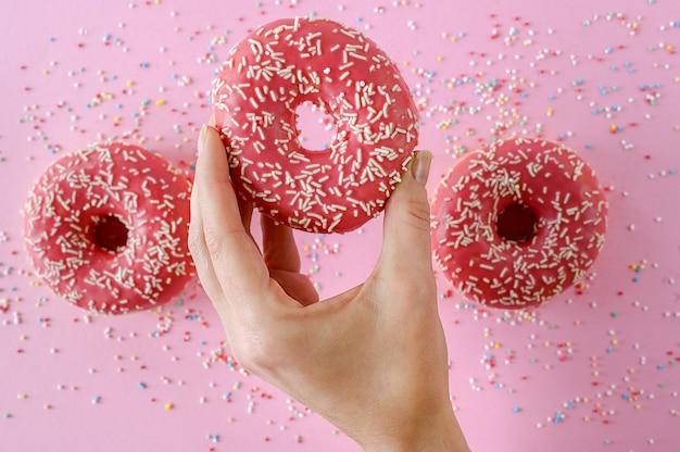 Frisch gebackene erdbeer-donuts in der hand