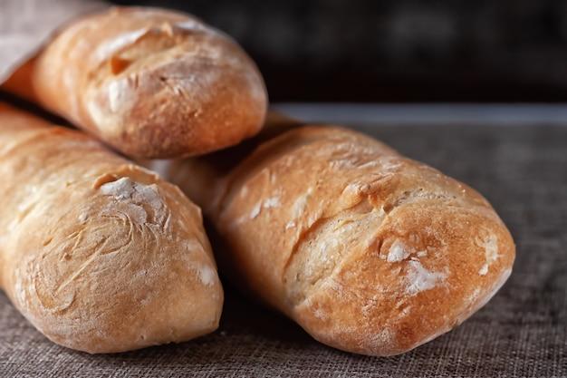Frisch gebackene französische baguettes auf einem mit stoff bedeckten tisch. selektiver fokus.