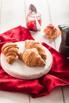Frisch gebackene französische croissants mit einem glas marmelade auf einer hellen holzoberfläche mit einer roten serviette.
