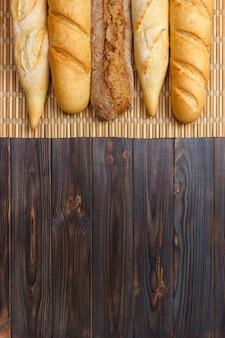 Frisch gebackene französische stangenbrote auf weißem holztisch. draufsicht, kopie, raum