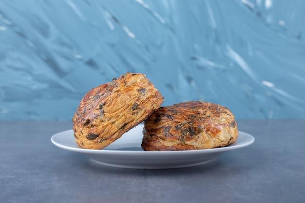 Frisch gebackene gogal-kekse auf einem teller auf marmortisch.