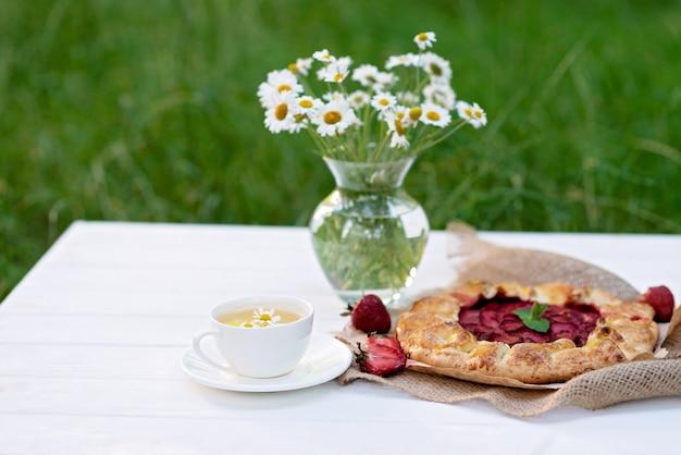 Frisch gebackene hausgemachte galette oder offene erdbeerkuchen, eine tasse kräutertee und eine vase mit einem blumenstrauß aus gänseblümchen.