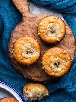 Frisch gebackene hausgemachte gewürzte bananenmuffins mit walnüssen auf hölzernem umhüllungsbrett auf rustikaler tabelle. gesunder snack für kinder. vertikales bild